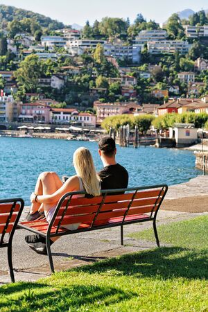 Couple sitting on the bench at the embankment of Ascona luxurious resort on Lake Maggiore, Ticino canton, Switzerland. Stock Photo