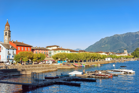 Ascona, Switzerland - August 23, 2016: St Peter and Paul church tower and colorful Swiss buildings at the luxurious resort in Ascona on Lake Maggiore, Ticino canton in Switzerland. Editorial