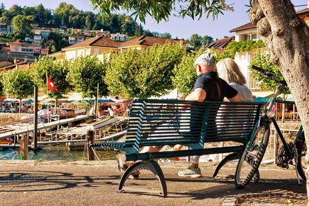 Couple sitting on the bench at the promenade of the luxurious resort in Ascona on Lake Maggiore of Ticino canton in Switzerland.