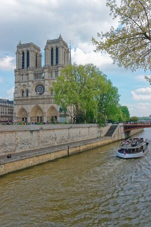 Paris, France - May 3, 2012: Notre Dame de Paris Cathedral, river boat and Seine River embankment in Paris, France. Or Cathedral of Our Lady of Paris in English. People on the background
