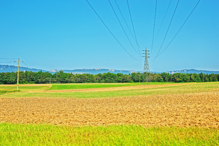 etl: Field and electric transmission lines in a Swiss village in Yverdon les Bains in Jura Nord Vaudois district of Canton Vaud, in Switzerland. Stock Photo