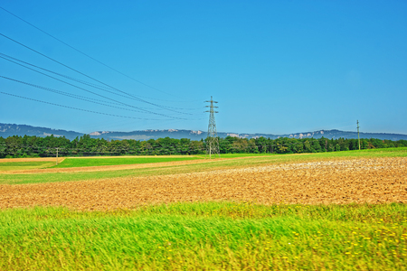 etl: Field and electric transmission lines in a Swiss village in Yverdon les Bains in Jura Nord Vaudois district of Canton Vaud, Switzerland.