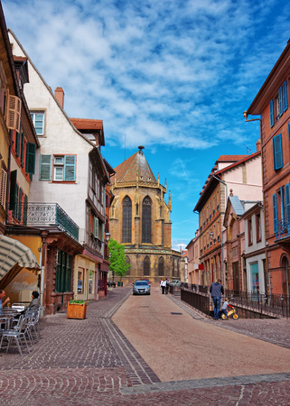 haut rhin: Colmar, France - May 1, 2012: Rue de Eglise Street and fragment of St Martin Church in Colmar, Haut Rhin in Alsace, France. People on the background