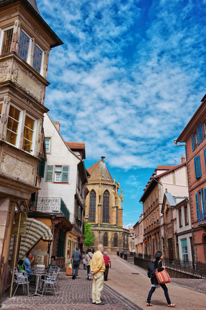 Colmar, France - May 1, 2012: Rue de Eglise Street and fragment of St Martin Church in Colmar, Haut Rhin in Alsace, France. People on the background