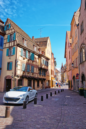 Colmar, France - May 1, 2012: Colorful Timber framing houses on Grand Rue Street in the Old city center of Colmar, Haut Rhin in Alsace, in France. People on the background Editorial