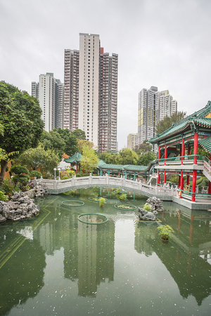 Small pond in God Wish Garden among Skyscrapers of the City in Wong Tai Sin Temple in Kowloon, in Hong Kong Stock Photo