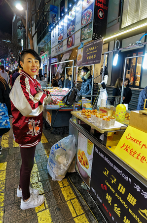 coking: Seoul, South Korea - March 14, 2016: Young girl buying sweet potato at the stall at Myeongdong open street market in Seoul, South Korea
