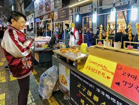 coking: Seoul, South Korea - March 14, 2016: Young girl buying sweet potato at the stall in Myeongdong open street market in Seoul, South Korea Editorial