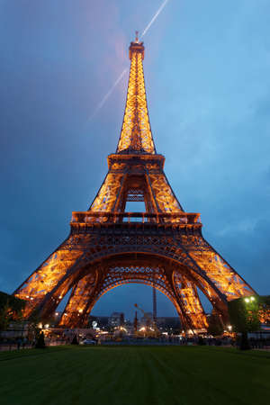 Paris, France - May 2, 2012: Eiffel Tower Illuminated in the evening in Paris in France. This cultural icon is placed on the Fields of Mars. People on the background