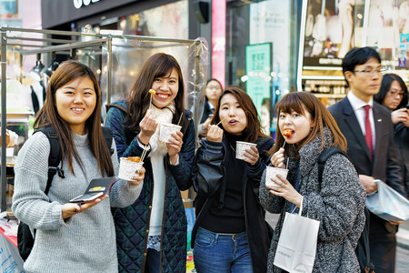 culinary tourism: Seoul, South Korea - March 14, 2016: Korean girls tasting street food at Myeongdong open street market, Seoul, South Korea Editorial