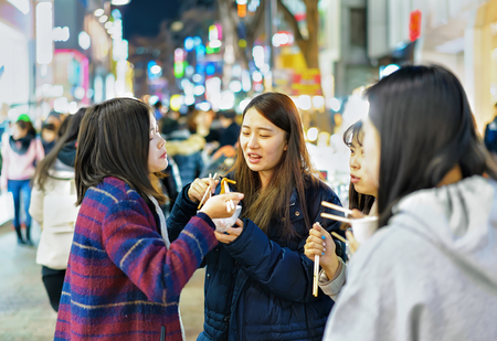 culinary tourism: Seoul, South Korea - March 14, 2016: Korean girls tasting street food at Myeongdong open street market in Seoul, South Korea Editorial