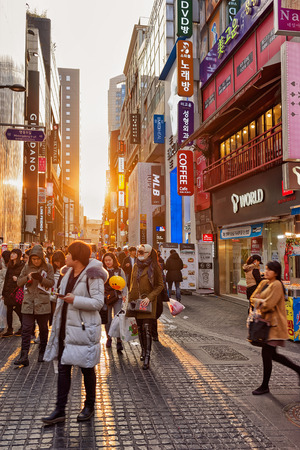 jung: Seoul, South Korea - March 14, 2016: Korean young people passing by in Myeongdong street market in Seoul, South Korea. At sunset