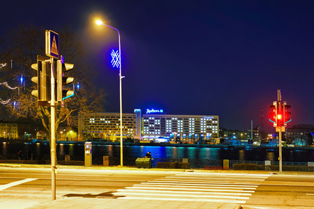 Riga, Latvia - December 24, 2015: Night look at the Daugava river and the Radisson Blu hotel in the background in Riga, Latvia. The hotel is one of the most famous and luxurious.