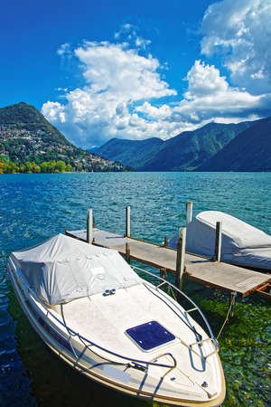 Motor Boats at the promenade of the luxurious resort in Lugano on Lake Lugano and Alps mountains, Ticino canton, Switzerland. Stock Photo