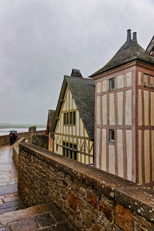 manche: Old Houses in Mont Saint Michel in Normandy region at Manche department of France. People on the background Stock Photo