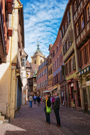 Colmar, France - May 1, 2012: Colorful Timber framing houses on Rue des Marchands Street in the Old city center of Colmar, Haut Rhin in Alsace, in France. People on the background