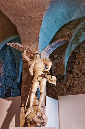 Mont Saint-Michel, France - May 8, 2012: Sculpture of St Michel with wings fighting and defeating dragon, Mont Saint Michel of Normandy region at Manche department in France.