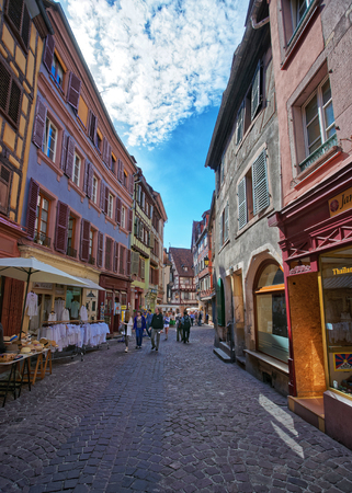 Colmar, France - May 1, 2012: Maison Pfister and other Colorful Timber framing houses on Rue des Marchands Street in the Old city center of Colmar, Haut Rhin in Alsace France. People on the background
