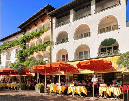 Ascona, Switzerland - August 23, 2016: Restaurants and cafes at the luxurious resort of Ascona on Lake Maggiore, Ticino canton, Switzerland. People on the background. Editorial