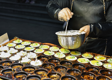 culinary tourism: Person is cooking food for selling at the stall with street food in Myeongdong open street market in Seoul, South Korea