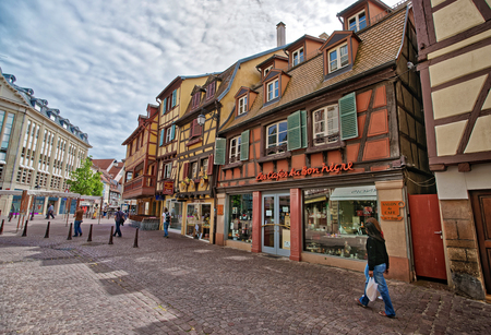 Colmar, France - May 1, 2012: Colorful Timber framing houses on Rue des Tetes Street in the old city center of Colmar, Haut Rhin in Alsace, in France. People on the background