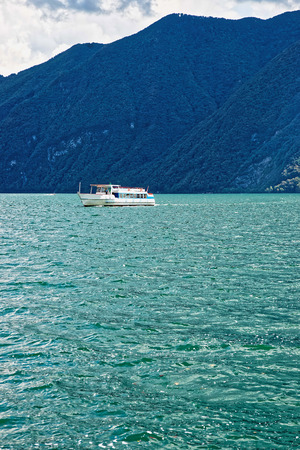 Small passenger ship at the promenade of the luxurious resort in Lugano on Lake Lugano and Alps mountains, Ticino canton, Switzerland. Stock Photo