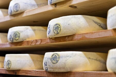 creamery: Stack of aging Cheese on wooden shelves in maturing cellar of Franche Comte creamery in France Stock Photo