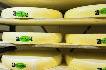 creamery: Stack of aging Gruyere de Comte Cheese on wooden shelves in ripening cellar of Franche Comte creamery in France. It is written - France, Comte, August 25, 2016