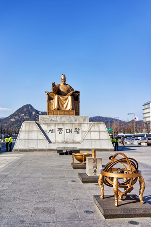 king street: Seoul, South Korea - March 11, 2016: Statue of the King Sejong in Gwanghwamun square in Seoul, South Korea. People in the street