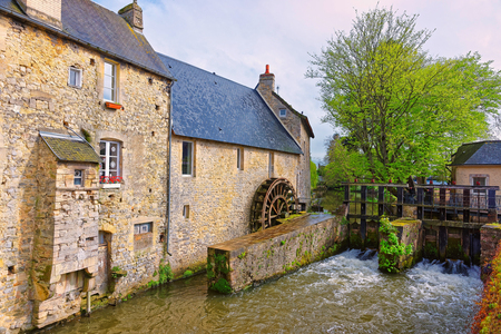 Water mill and Aure River in the old city of Bayeux in Calvados department at Normandy, France. Stock Photo