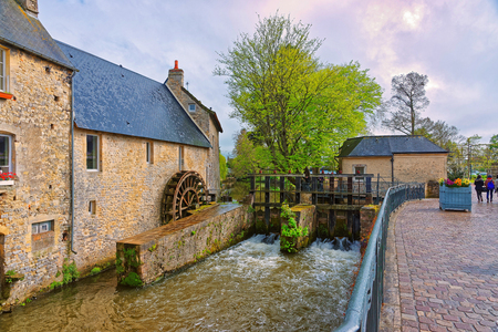 Water mill and Aure River in the old city of Bayeux in Calvados department in Normandy, France. People on the background