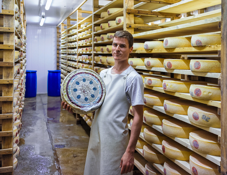 gruyere: Evillers, France - August 31, 2016: Worker holds a wheel of Gruyere de Comte Cheese in ripening cellar at Franche Comte creamery in France Editorial