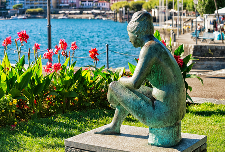 Ascona, Switzerland - August 23, 2016: Sitting woman statue at the promenade of the luxurious resort in Ascona on Lake Maggiore of Ticino canton, Switzerland. People on the background. Editorial