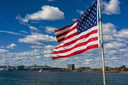 City skyline and flag of the United States of America in Boston, USA. It is one of the main symbols of the country and consists of 13 horizontal stripes with 50 small stars for each state. Stock Photo