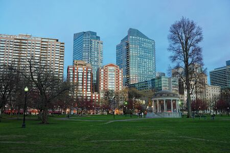 Boston, USA - April 27, 2015: Skyline and Boston Common public park in downtown Boston, Massachusetts, the United States. People on the background. Late in the evening