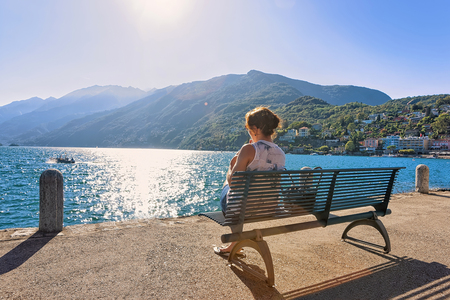 Woman sitting on the bench at the embankment of the expensive resort at Ascona on Lake Maggiore, Ticino canton, Switzerland. Stock Photo