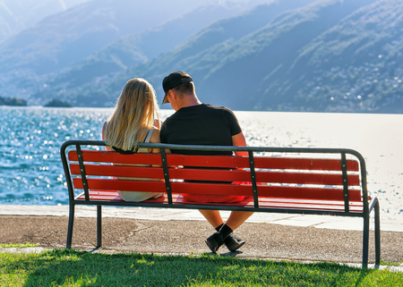 Couple sitting on the bench at the promenade of the expensive resort in Ascona on Lake Maggiore, Ticino canton of Switzerland.