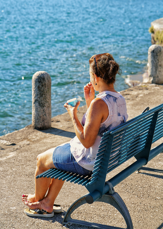 Woman eating ice cream and sitting on the bench at the embankment in the expensive resort in Ascona on Lake Maggiore, Ticino canton, Switzerland. Stock Photo