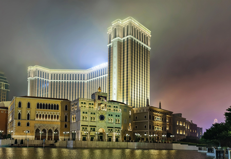 Macao, China - March 8, 2016: Waterfront and Venetian Macau Casino and luxury resort of Macao, China. Late in the evening. Golden light illumination