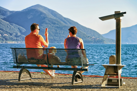 Ascona, Switzerland - August 23, 2016: Couple eating ice-cream and sitting on the bench at the embankment of the expensive resort in Ascona on Lake Maggiore, Ticino canton, Switzerland.