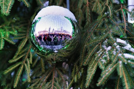 poquito: Christmas ball on green Christmas tree covered with a little bit of snow.