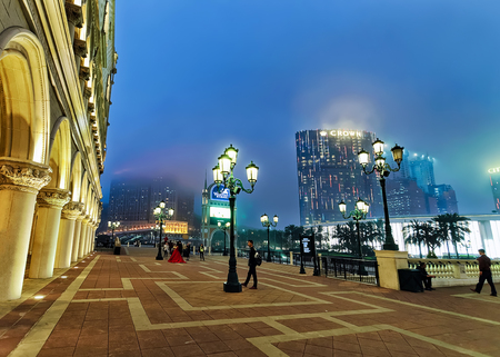 dreams of city: Macao, China - March 8, 2016: Embankment of Macau Casino and Hotel luxury resort in Macao in China. Late in the evening. Golden light illumination. City of Dreams and People are on the background
