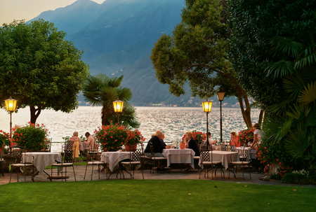 restaurant dining: Ascona, Switzerland - August 23, 2016: People dining at the typical sidewalk restaurant at the luxurious resort in Ascona on Lake Maggiore, Ticino canton, Switzerland. Late in the evening