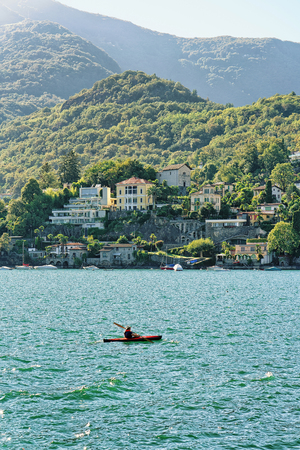 cayak: Ascona, Switzerland - August 23, 2016: Man in cayak in the Boat in Ascona on Lake Maggiore in Ticino canton in Switzerland.