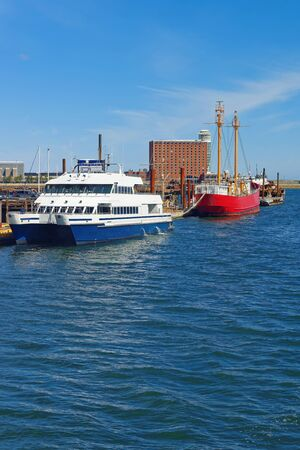 seaports: Moored ships and boats near the pier in Boston, USA. The Port of Boston is one of the most important seaports in the east coast of the United States and Massachusetts state.