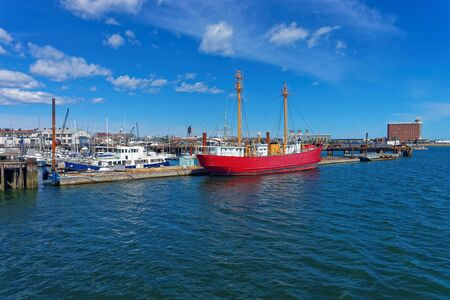 Moored red ship near the pier in the Port of Boston in the city of Boston, USA. The port is one of the major seaports in the east coast of USA and in the state Massachusetts.