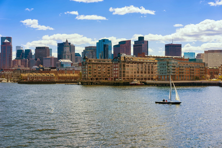 Lonely sailboat floating across the river Charles in front of the skyline of Boston, USA. The city is one of the oldest in the United States. It was founded in 1630 by Puritan immigrants.