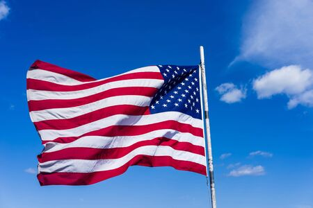 13: National flag of the United States in front of the sky in Boston, USA. It consists of 13 horizontal stripes and 50 white stars. Each star symbolizes the state in the US.