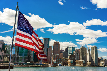 Beautiful city and American flag in Boston, United States. It is one of the main symbols of the country. Flag includes thirteen horizontal stripes and fifty small white stars for each state.