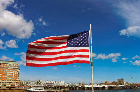 City skyline and flag of the United States in Boston, USA. The national symbol consists of 13 stripes and 50 small white stars which represent each state of the country.
